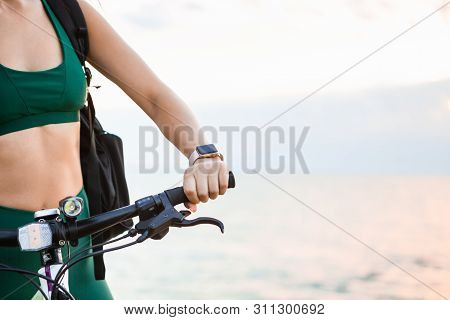 Beautiful Young Brunette Woman Resting After Bicycle Ride At Sunrise. Smart Watch For Pulse Check Of