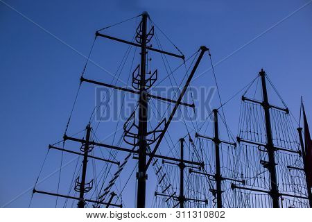 Silhouettes Of Frigate Masts Against The Blue Sky In The Evening. Mast Yacht At Dusk. Masts Of A Pir