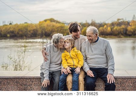 Senior Couple With With Grandson And Great-grandson In The Autumn Park. Great-grandmother, Great-gra