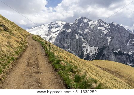 Mountain Trail With A View Of The Marmolada Massif. Dolomites. Italy.