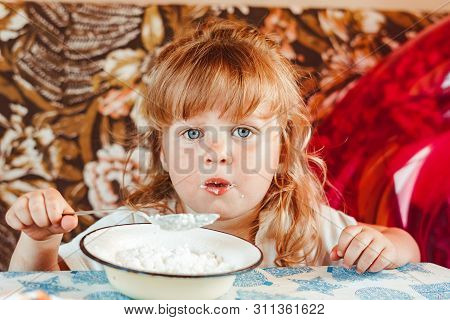Happy Little Girl Eating A Spoonful Of Cottage Cheese While Sitting At The Table