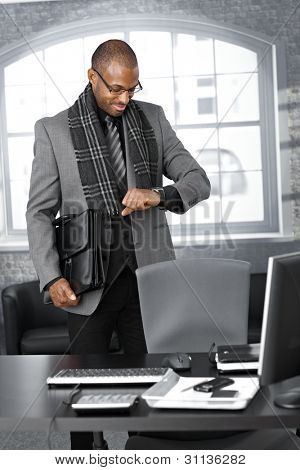 Smiling businessman checking time on watch at office, standing by desk with briefcase ready to leave.
