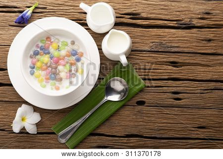 Thai Sweets And Colorful Ball Flour In A White Spoon On A Banana Leaf, Coconut On An Old Wooden Tabl