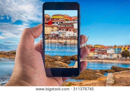 Hand Taking Picture With A Smartphone On The Beach Inside The Village Of Porto Torres, Sardinia
