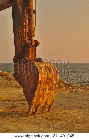 Close-up Of A Big Rusty Excavator Bucket In Front Of The Blue Mediterranean Sea And The Pink Sky At