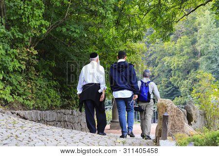 Older Hasidic Jews Walk In The Sofia Park During The Jewish New Year In Uman, Ukraine. Religious Jew