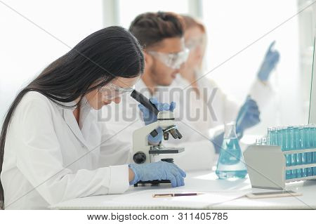 Close Up.scientists And Laboratory Workers Sitting At The Laboratory Table