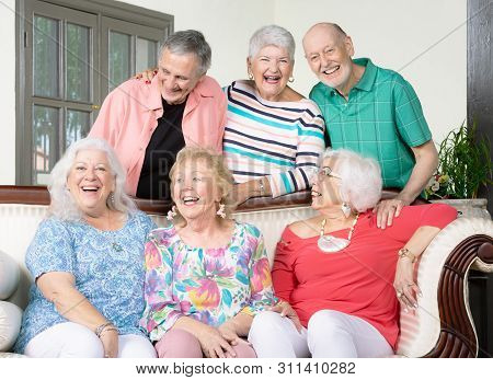 Six Laughing Senior Friends Around An Antique Couch