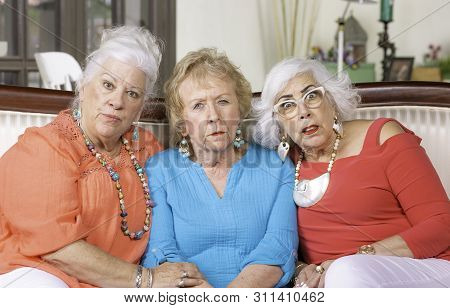 Three Skeptical Or Shocked Senior Women On Couch