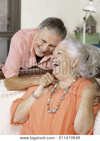 Senior Man And Woman At Home On Couch Smiling