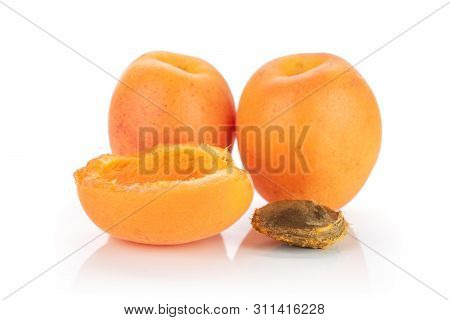 Group Of Two Whole One Half Of Meaty Fresh Deep Orange Apricot With A Stone Isolated On White Backgr