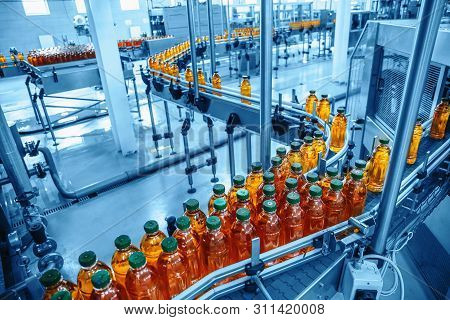 Conveyor Belt, Juice In Bottles On Beverage Plant Or Factory Interior In Blue Color, Industrial Prod