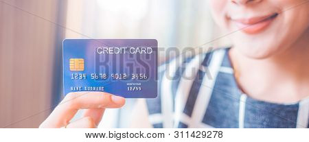 Woman Hand Holds A Blue Credit Card.she Smiled Happily.