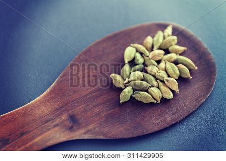 Dry Cardamom Seeds On A Brown Wooden Spatula. Natural Food Spices And Seasonings. Tasty Eating. Clos