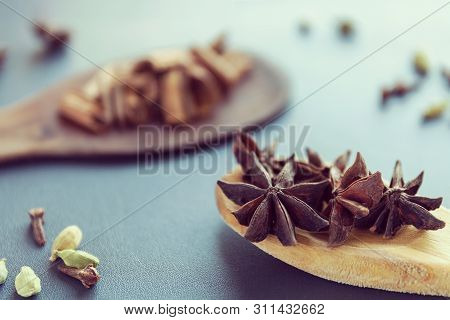 Dry Star Anise Clove Cinnamon And Cardamom On A Brown Wooden Spatula. Natural Food Spices And Season