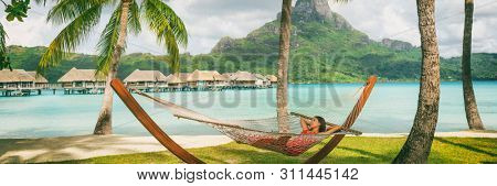 Luxury vacation hotel panoramic Asian woman sleeping in hammock by overwater bungalow resort Bora Bora, Tahiti, French Polynesia. summer travel. relaxation getaway.