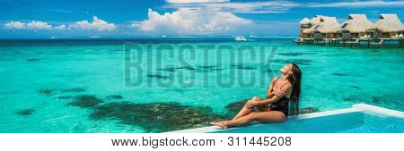 Suntan beach vacation luxury woman sunbathing by overwater bungalow infinity hotel pool. Sexy Asian swimsuit model beauty banner panoramic on ocean blue beach background.