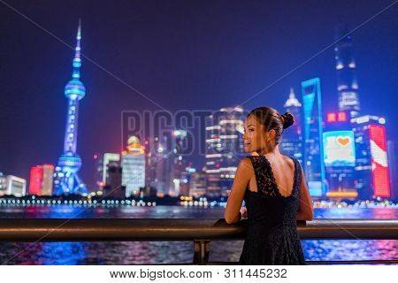 Shanghai city night lights glowing in dark sky. Elegant lady by the Bund river in fancy lace dress evening gown. Asian model sightseeing.