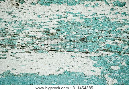 Peeling paint of green color on the wooden texture background