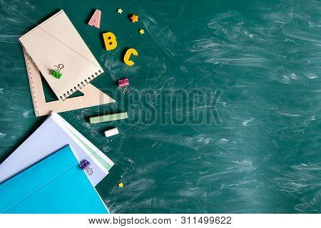 Still Life With School Supplies. Blackboard In Chalk Chalkboard. Green Background. Notebooks, Notebo