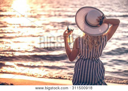Girl Wearing Striped Dress Walking Standing And Holding A Hat And A Cocktail On The Sea Shore. Marin