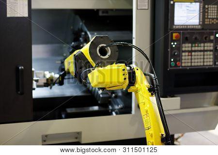 Robot Arm Is Loading Detail Into Cnc Lathe Machine. Selective Focus.