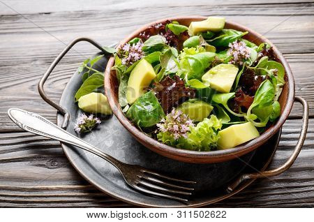 Clay Dish With Salad Of Avocado, Green And Violet Lettuce, Lamb's Lettuce And Oregano Flowers With V