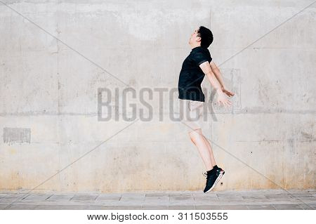 Side View Of Asian Male In Sportswear Jumping In The Air Against Shabby Wall During Outdoor Workout