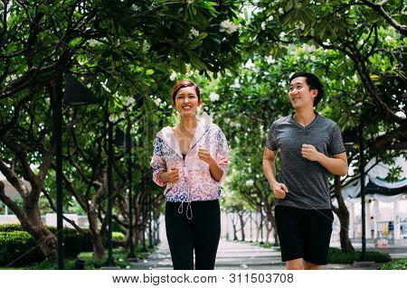 Asian Man And Woman In Sportswear Smiling And Running Together On Alley In Green Park On Sunny Day