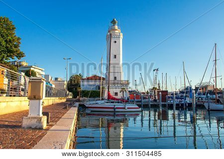 Lighthouse In Sea Port Of Rimini, Italy. Boats Moored In The Harbor Channel In Rimini, Italy