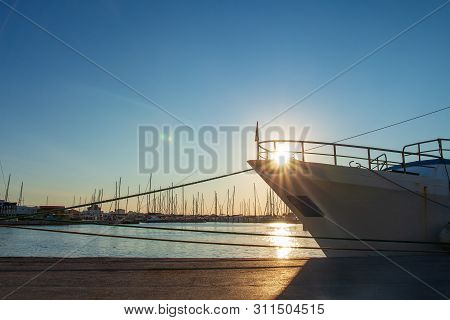 Ship Moored In The Harbor Channel In Rimini At Sunset, Italy. Sun And Ship In Sea Port