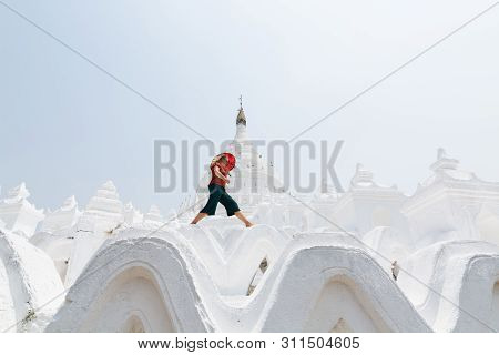 Blonde Caucasian Woman With Red Umbrella Walking On The Walls Of Myatheindan Pagoda In Mandalay, Mya