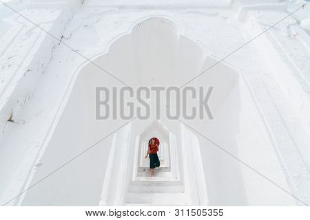 Blonde Caucasian Woman With Red Umbrella Walking On The Terraces Of Myatheindan Pagoda In Mandalay,