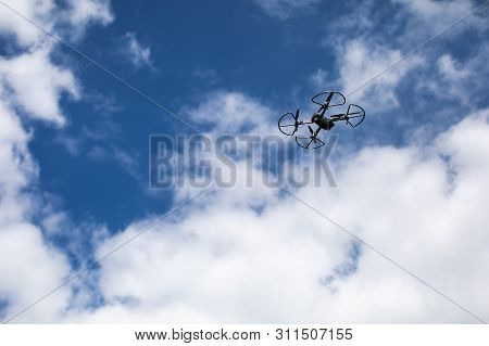 Drone Quadcopter With Digital Camera On Blue Sky Background