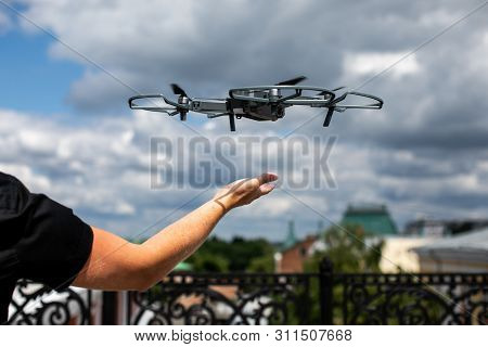 Drone Landing On Hand. Drone And Photographer Man Hands.drone Copter Flying With Digital Camera