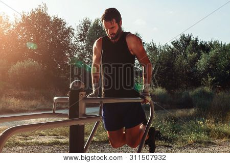 Boxer Athlete In Outdoor Training Doing Pushups At The Dip Station. Sport, Healthy Life And Strength