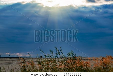 Dry Grass On The River Sand On The River Bank Against The Background Of A Stormy Sky, Dark Clouds Wi