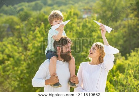 Happy Family On Holiday. Happy Family With Kid On Summer Field - Dream Of Flying Concept. Happy Lovi