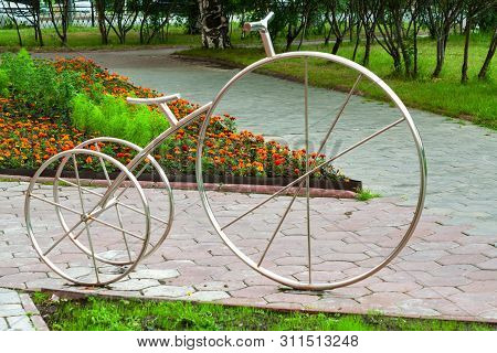 A Parking Place For Bicycles, Metal Bicycle Sign On The Background Of Flower Beds, Cityscape