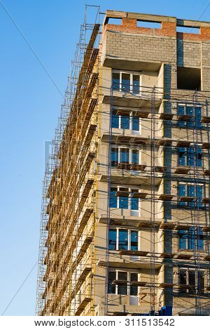 Construction Of A Multi-storey Residential Building, A House In The Scaffolding, Illuminated By The