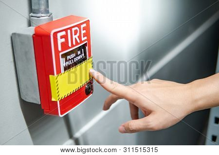 Male Hand Pointing At Red Fire Alarm Switch On Concrete Wall In Factory. Industrial Fire Warning Sys