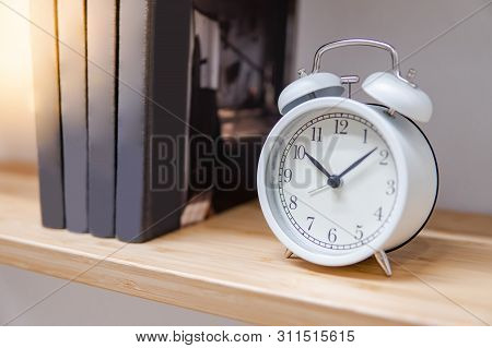 White Table Clock And Books On Wooden Bookshelf In Living Room. Home Decoration. Time Concept