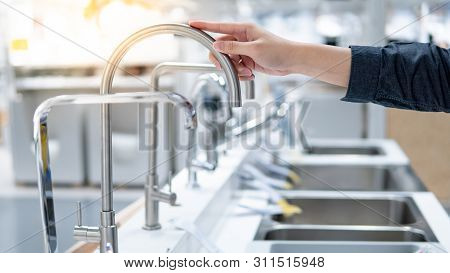 Male Hand Choosing Stainless Steel Water Tap In Furniture Store. Home Improvement For Domestic Kitch