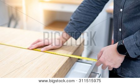Male Hand Interior Designer Using Tape Measure For Measuring Size Of Wooden Countertop In Modern Kit