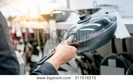 Male Hand Choosing Cooking Pan With Glass Lid In The Kitchen Store. Buying Cookware Or Kitchenware C
