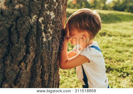 Outdoor Image Of Cute Little Boy Covering His Eyes With Hands, Playing Hide And Seek Standing Next A