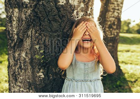 Horizontal Outdoor Image Of Smiling Little Girl Covering Her Eyes With Both Hands, Playing Hide And