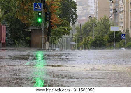 At The Crossroads Of The Road, The Green Light Of A Traffic Light Is Lit In The Pouring Rain On A Ci