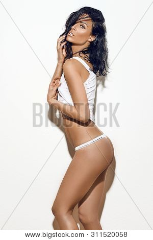 Sexy Middle-aged Slim Woman In White Underwear Posing Over A White Studio Background With Copy Space