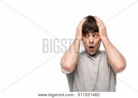 Young Discouraged Man Holding Hands On Head While Looking Away Isolated On White
